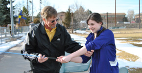 Teacher and coach Mark Smith helps a student better her golf swing. Photo by Henna Danek